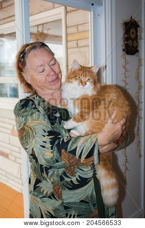 Smiling older woman with a big orange cat