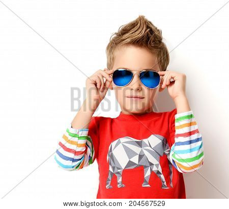 Happy young boy standing in fashion red shirt looking at the corner in sunglasses positive attitude, full lenght on white background