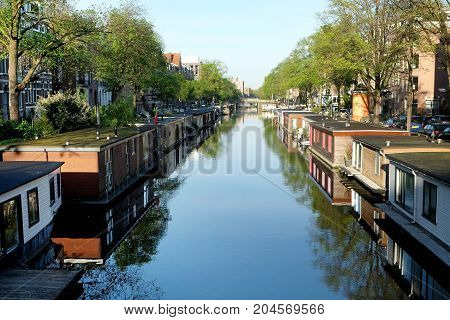 AMSTERDAM NETHERLANDS - MAY 14 2017: Houseboat on the canal in the historic part of Amsterdam