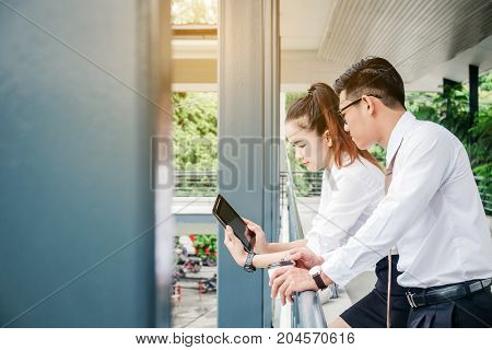 Business Man And Woman With Tablet Computer Standing Talking And Viewing Documents Outdoor