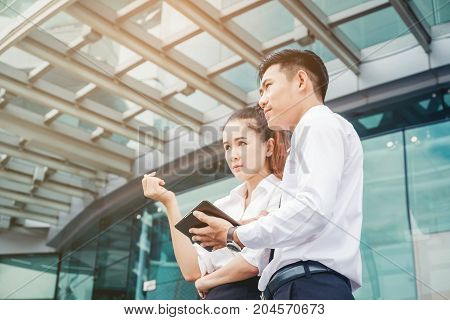 Asian Business Couple Meeting Using Digital Tablet Outdoor Standing In Outdoor Office