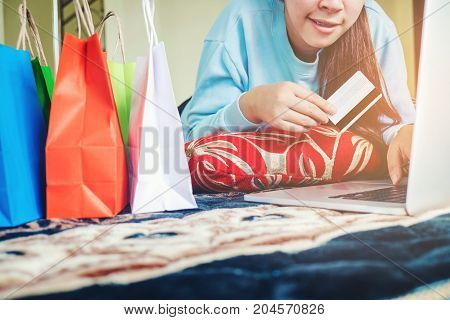 Woman Shopping Online Using Laptop With Credit Card Enjoying In Home