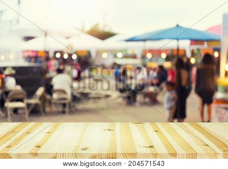 Blurred photo of food exhibition fair montage with wood table top for background.
