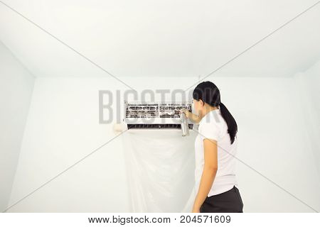 Woman cleaning air conditioner by foam cleaning agent.