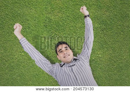 High angle view of a young man resting and lying down on the green grass
