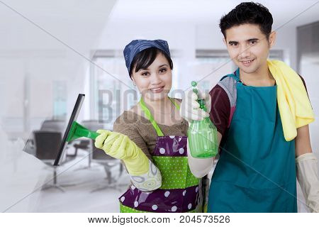 Pictur of young couple cleaning a mirror with a spray and squeegee while standing in the office