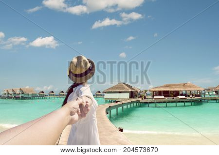 Back view of a female tourist holding hand of her husband while leading to bungalow in the tropical beach