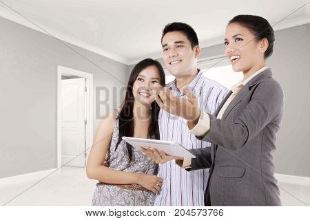Picture of a female real estate agent holding a digital tablet while explaining new property to her customer