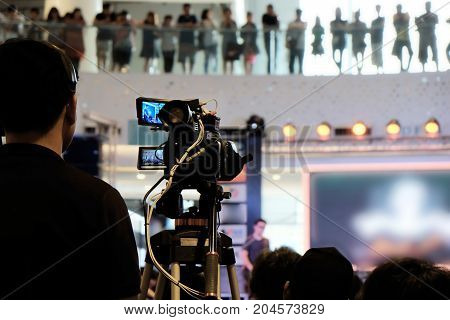 Videographer man working in live event concert hall.