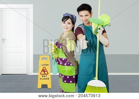 Image of two janitors showing thumbs up while standing with cleaning equipment in the hotel