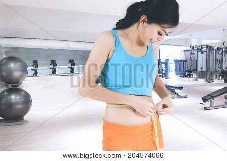 Sporty woman measuring her slim waist with a measuring tape while standing in the fitness center
