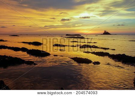 Beautiful sea sunset with small island silhouette on the beach at low tide & rock on the shore of the sea.