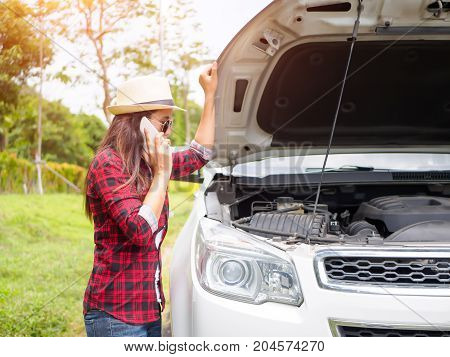 Young woman standing on the side of the road with broken car and calls the evacuation service.