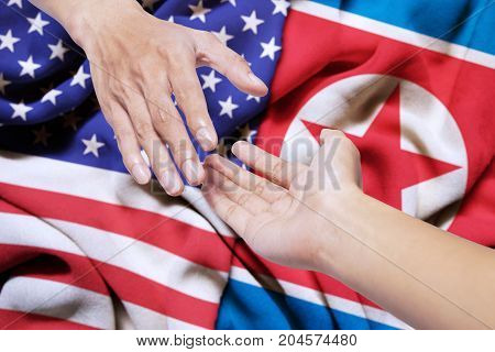 Symbolizing of peace. Hand of North Korea gives a help for a hand of the United States
