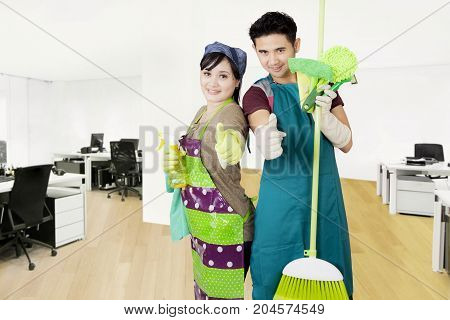 Two janitors showing thumbs up while standing with cleaning equipment in the office