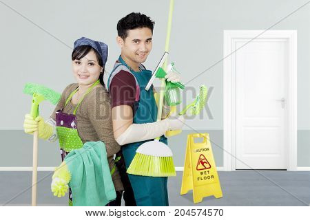 Image of two janitors holding cleaning equipment while standing in the hotel
