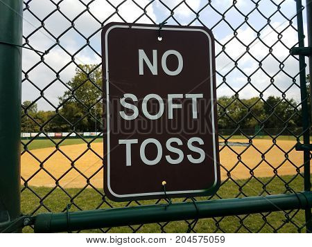 a black no soft toss sign on metal fence at baseball field