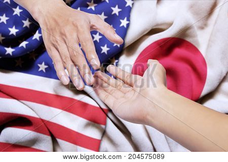 Hand of a person offering a help for somebody with Japan and USA flag in the background