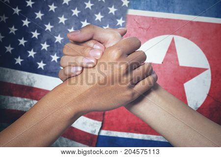 Symbolizing of peace. Two hands of people posing partnership with North Korea and United States flag in the background