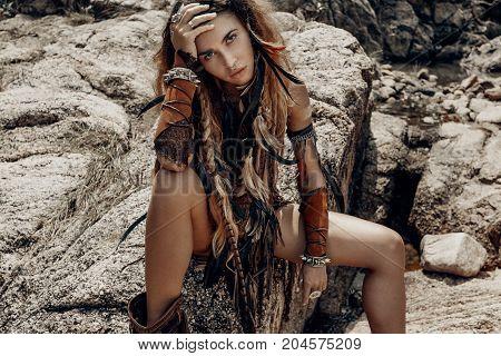 wild amazon woman sitting on the rocks