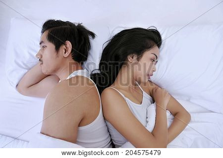 Upset Asian Couple Having Problems With Lying Side By Side In Bed Facing In Opposite Directions