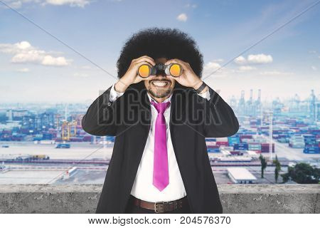 Picture of Afro businessman looking at the industrial port with a binocular while standing on the rooftop