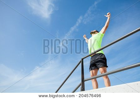 Cheerful young muscular man wearing sportswear, pumping fists, raising arms and standing at railing. Low angle view.