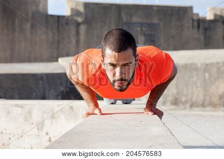 Closeup portrait of focused young strong handsome man wearing sportswear and doing push-ups on parapet with concrete constructions in background. Front view.