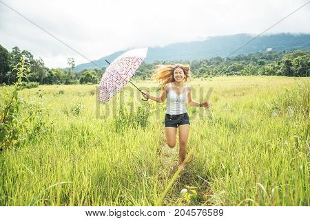 Asian women travel relax in the holiday. Running umbrella sunshine on a green pasture.