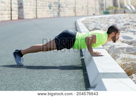 Focused young strong handsome man wearing sportswear and doing push-ups on road curb. Side view.