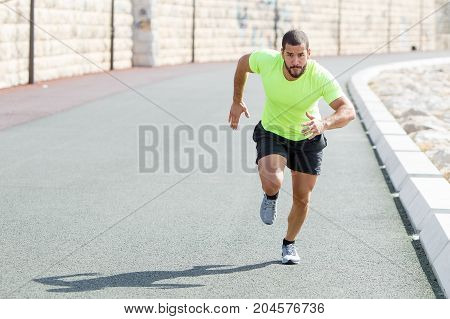 Portrait of focused young strong man wearing sportswear and running fast on road. Front view.