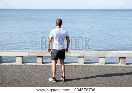 Pensive young handsome muscular man wearing sportswear, standing on bridge and looking at sea. Back view.