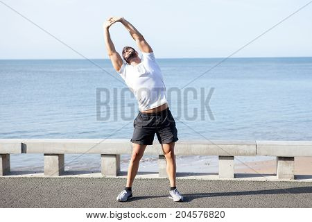 Serious young handsome strong man wearing sportswear, stretching body, doing side bend exercise and standing on bridge with sea in background. Front view.
