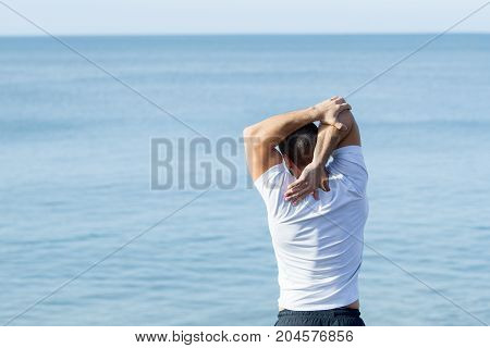 Closeup of young handsome muscular man wearing sportswear and stretching arm with sea in background. Back view.