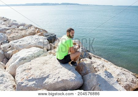 Pensive young handsome strong man looking away and sitting on stones on sea shore