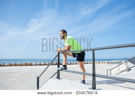 Portrait of young handsome strong man wearing sportswear, looking straight, relaxing and leaning on railing at seaside