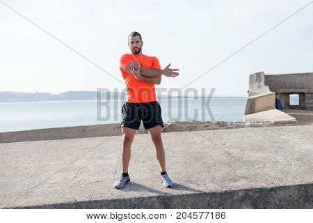 Serious young handsome strong man wearing sportswear, looking at camera, standing on concrete platform and stretching arm with river in background. Front view.