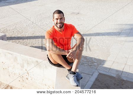 Portrait of smiling young handsome strong man wearing sportswear, looking at camera and sitting on parapet. High angle view.