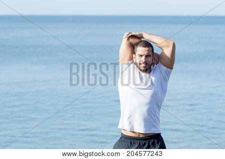 Closeup portrait of young handsome muscular man wearing sportswear and stretching arm with sea in background. Front view.
