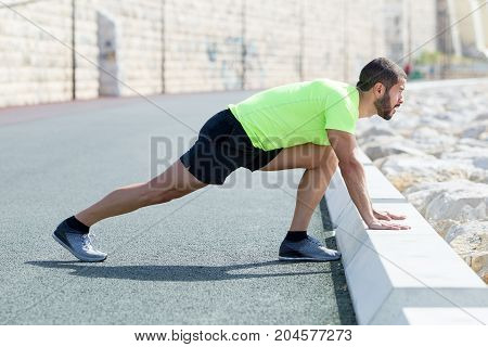 Determined young strong handsome man wearing sportswear, standing on road, stretching calf and leaning on curb. Side view.