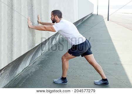 Serious young strong handsome man wearing sportswear, standing on pavement, stretching calf and leaning on concrete wall. Side view.