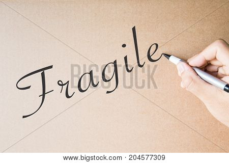 hand writing fragile on brown paper background