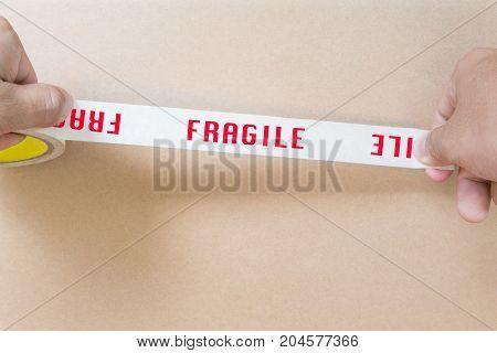 hand holding fragile tape on carton box