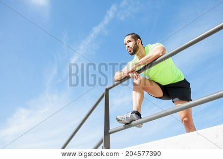 Portrait of young handsome strong man wearing sportswear, looking straight, relaxing and leaning on railing. Low angle view.