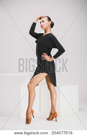 pretty woman in black dress posing in studio, dancer showing pose