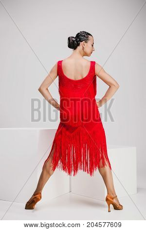 young girl in red dress in studio, beautiful dancer turning backwards