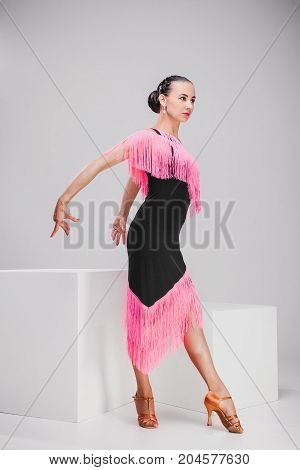 elegant woman in pink and black dress posing in studio, pretty girl showing one movement from dance
