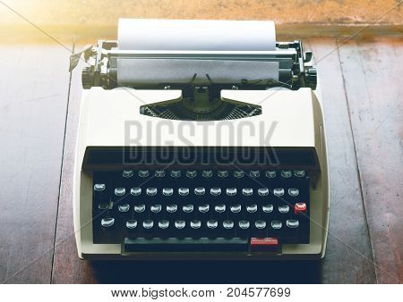Old vintage typewriter with white blank paper on wooden brown table