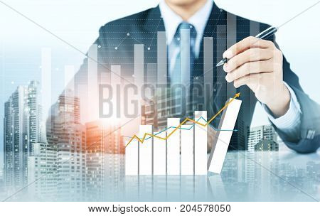 Businessman write increasing graph with city background, business growth