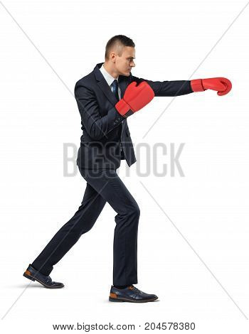 A businessman stands in side view on white background and throws punches wearing red boxing gloves. Fight for promotion. Career path. Aggressive competition.
